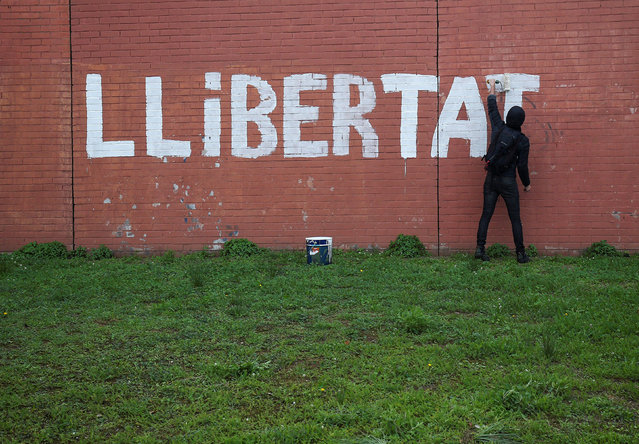 """A man paints the word """"Freedom"""" on a wall as protesters blocked a ring road in Barcelona during a partial regional strike called by pro-independence parties and labour unions in Barcelona, Spain, November 8, 2017. (Photo by Albert Gea/Reuters)"""