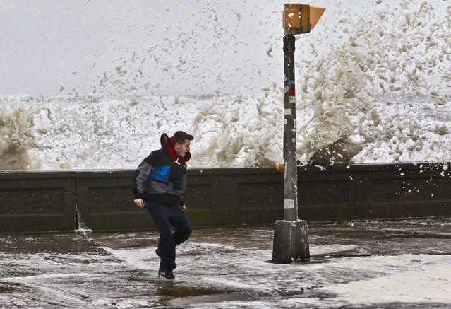 A man reacts to waves crashing over a seawall in Narragansett, Rhode Island. (Photo by Steven Senne/Associated Press)