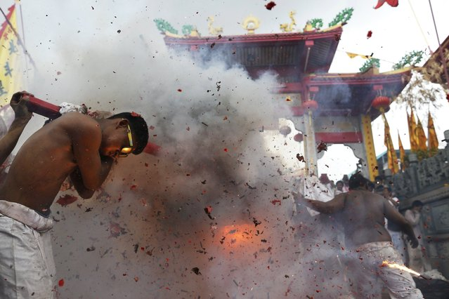Firecrackers explode as devotees of the Chinese Jui Tui Shrine return the statue to the shrine after a procession celebrating the annual vegetarian festival in Phuket September 30, 2014. The festival, featuring face-piercing, spirit mediums and strict vegetarianism celebrates the local Chinese community's belief that abstinence from meat and various stimulants during the ninth lunar month of the Chinese calendar will help them obtain good health and peace of mind. (Photo by Damir Sagolj/Reuters)