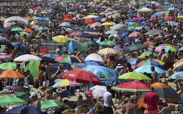 Crowds gather on the beach in Bournemouth, England, Thursday June 25, 2020, as coronavirus lockdown restrictions have been relaxed. According to weather forecasters Thursday could be the UK's hottest day of the year, so far, with scorching temperatures forecast to rise even further. (Photo by Andrew Matthews/PA Wire via AP Photo)