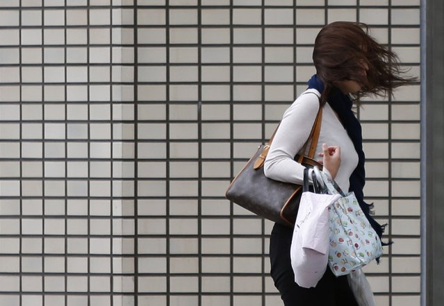 A woman's hair blows across her face as she struggles to walk in a strong wind caused by Typhoon Phanfone on a street in Tsu, Mie Prefecture, western Japan October 6, 2014. Hundreds of flights were cancelled and thousands of people advised to evacuate as a powerful typhoon lashed Japan on Monday with heavy rains and high winds, leaving at least one person dead as it headed towards Tokyo. (Photo by Yuya Shino/Reuters)