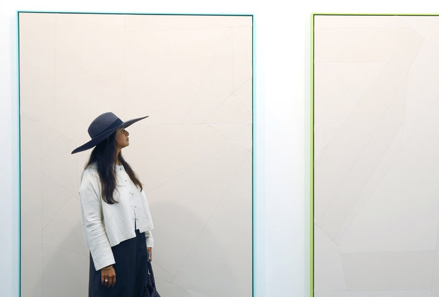 A visitor poses with untitled works by artist Sarah Crowner at the Frieze Art Fair in London, October 14, 2014. (Photo by Luke MacGregor/Reuters)