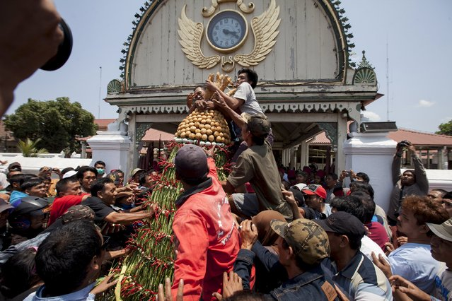 People scramble towards food, that has been put together to resemble a mountain, during the Grebeg Besar ceremony to mark Eid al-Adha in front of the Great Mosque, in Yogyakarta September 24, 2015. (Photo by Dwi Oblo/Reuters)