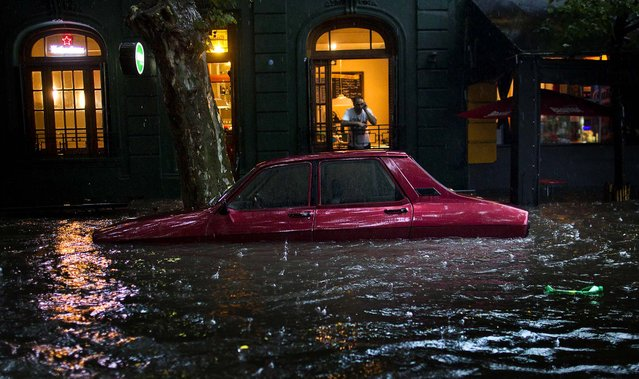 A car is submerged in floodwater in front of a home in Buenos Aires, Argentina, December 6, 2012. (Photo by Natacha Pisarenko/Associated Press)