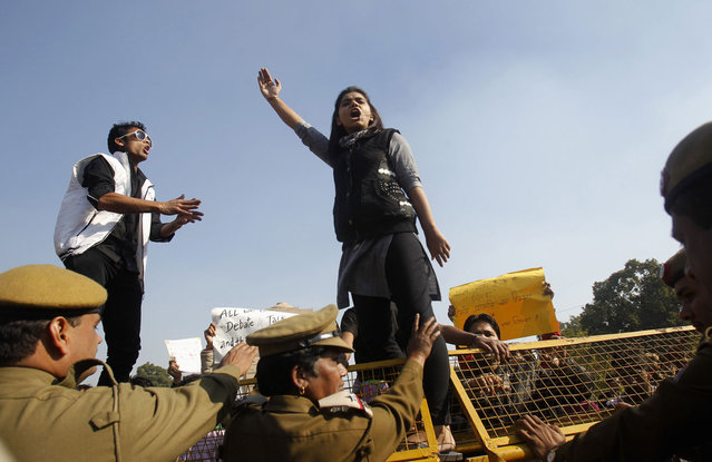 A demonstrator stands on a barricade erected by police and shouts slogans during a protest rally organized by various women's organizations in New Delhi, on December 21, 2012. (Photo by Mansi Thapliyal/Reuters)