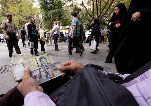 A money changer displays U.S. and Iranian banknotes at the Grand Bazaar in central Tehran October 7, 2015. (Photo by Raheb Homavandi/Reuters)