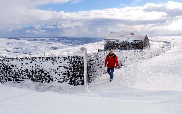 A man walks through snow near Castleton, England, Novovember 25, 2010. (Photo by John Giles/Press Association)