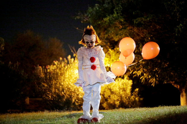 """A boy dressed as Pennywise the Dancing Clown from the movie """"It"""" poses for a photo during a Halloween party in Ciudad Juarez, Mexico, October 27, 2017. (Photo by Jose Luis Gonzalez/Reuters)"""