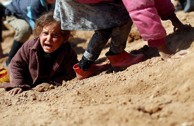 A displaced Iraqi girl cries before entering Hamam al-Alil camp, as Iraqi forces battle with Islamic State militants, south of Mosul, Iraq, March 10, 2017. (Photo by Suhaib Salem/Reuters)