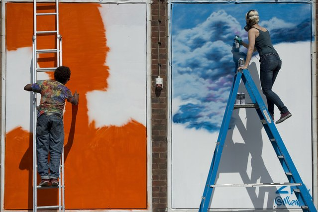 "Street artists create artworks, as they take part in the ""Sand Sea & Spray"" Urban Art Festival in Blackpool, north west England on July 11, 2015. (Photo by Oli Scarff/AFP Photo)"