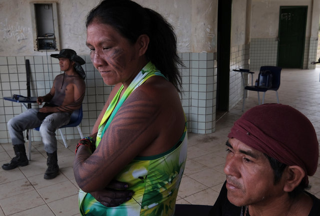 Guardian of the Forest members, from left: Francisco Neto Guajajara, 24, Juracy Paulino Guajajara and Ornil Paulino Guajajara, 55, hang out in a school building in Araribóia Indigenous Reserve, Maranhão, Brazil on August 7, 2015. (Photo by Bonnie Jo Mount/The Washington Post)