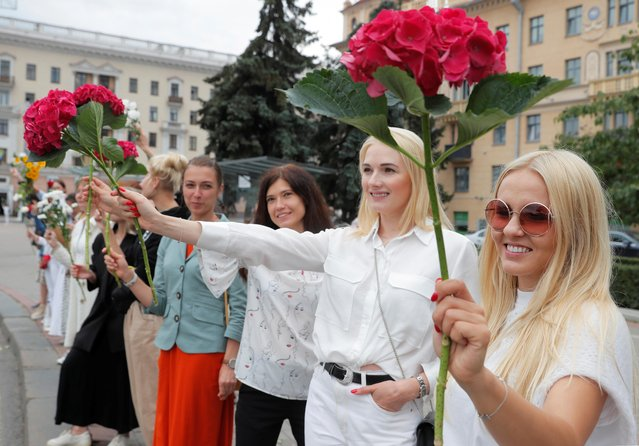 Women hold flowers during a demonstration against violence following recent protests to reject the presidential election results in Minsk, Belarus on August 20, 2020. (Photo by Vasily Fedosenko/Reuters)