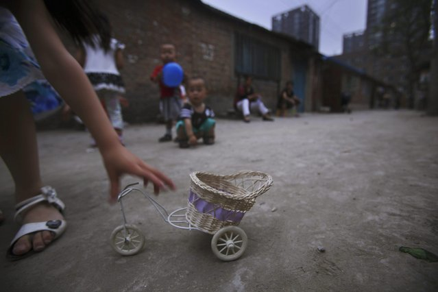 A Chinese girl, reaches for her toy, while playing outside her house along with other children, in a Hutong, or a traditional alleyway of Beijing, China, Sunday, June 13, 2010. (Photo by Muhammed Muheisen/AP Photo)