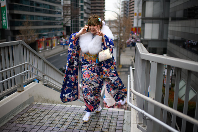 A woman wearing a kimono gestures at the camera as she leaves after attending a Coming of Age ceremony on January 8, 2018 in Yokohama, Japan. (Photo by Carl Court/Getty Images)