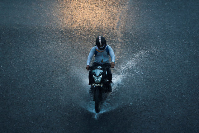A man rides a motorbike during heavy rains in New Delhi, India on August 17, 2020. (Photo by Adnan Abidi/Reuters)