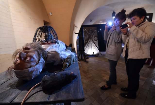 """Visitors take photos of an installation of the exhibition """"Torture and Execution in the Middle Ages"""" during its opening in Kiev on October 7, 2015. (Photo by Sergei Supinsky/AFP Photo)"""