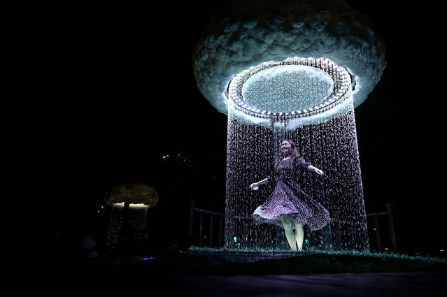 A woman dances as she visits an outdoor light immersive experience exhibition during the 2020 Beijing International Light Festival at a park in Beijing on August 22, 2020. (Photo by Wang Zhao/AFP Photo)