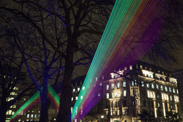 "Members of the public look at ""Spectral"", by Katarzyna Malejka and Joachim Slugocki in St James's Square during ""Lumiere London"" festival of light 2018 on January 18, 2018 in London, England. (Photo by Dan Kitwood/Getty Images)"