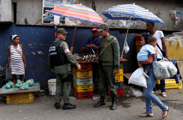 Members of the national guard are seen as they relocate street vendors during a routine patrol at the market in Petare neighborhood in Caracas, Venezuela July 14, 2016. (Photo by Carlos Jasso/Reuters)