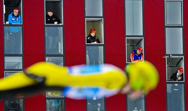 Judges look out of  their boxes as they watch Denis Kornilov of Russia take his jump during the single competition at the FIS Team Tour World Cup ski jumping in Klingenthal, Germany, on February 13, 2013. (Photo by Jens Meyer/Associated Press)