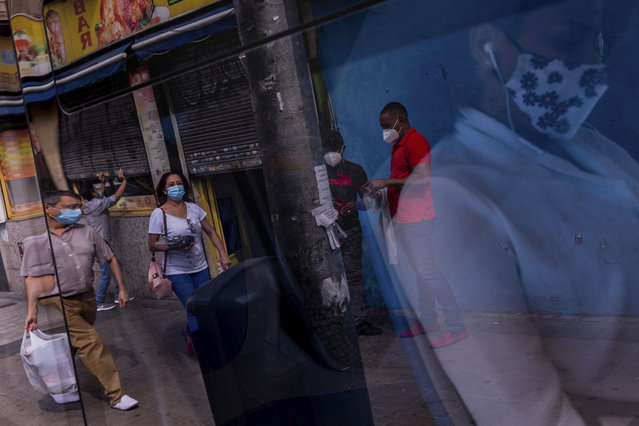 Pedestrians wear face masks to prevent the spread of coronavirus in the southern neighborhood of Vallecas in Madrid, Spain, Wednesday, September 16, 2020. The Spanish capital will introduce selective lockdowns in urban areas where the coronavirus is spreading faster, regional health authorities announced on Tuesday. The measures in Madrid will most likely affect southern, working-class neighborhoods where virus contagion rates have been steadily soaring since August. (Photo by Bernat Armangue/AP Photo)