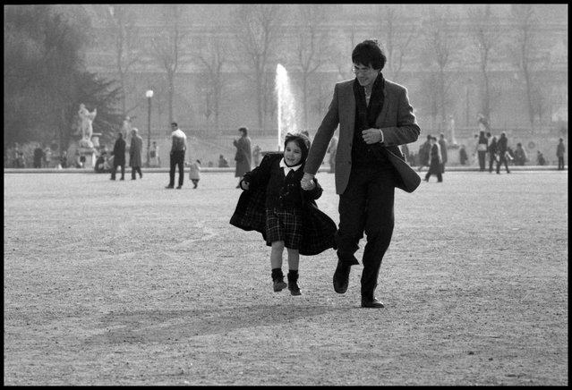 A Wednesday with papa, Paris. A father and daughter run through the Tuileries Gardens in Paris on a Wednesday afternoon when French children have the afternoon off from school. It is always a day when the Paris parks are full of wonderful scenes of parents and grandparents with their children. 1980ties. (Photo and comment by Peter Turnley)