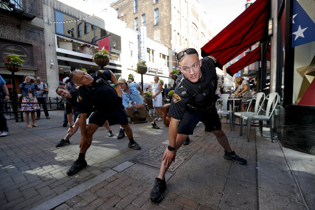 Police officers stretch and warm up before going on patrol, Wednesday, July 20, 2016, in Cleveland, during the third day of the Republican convention. (Photo by Alex Brandon/AP Photo)