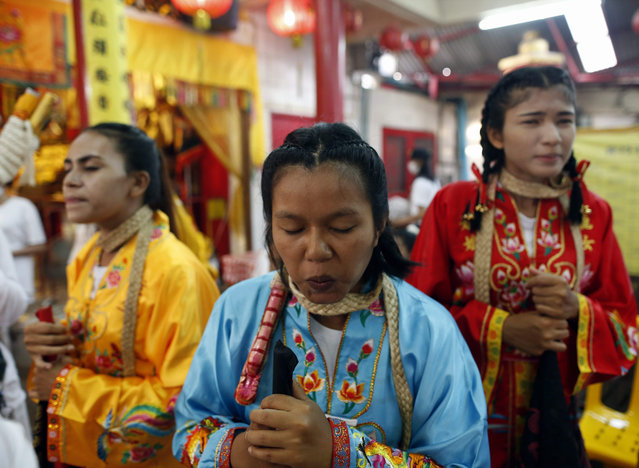 Female devotees to the Chinese Shrine of Jui Tui work themselves into a state of trance prior to a street parade during the annual Vegetarian Festival on Phuket Island, Thailand, 19 October 2015. The festival, which has Chinese origins, is held during the ninth lunar month of the Chinese calendar and it involves the beliefs of cleansing the body, ritual piercing, spirit medium, and the consumption of only vegetarian food as well as making merit. (Photo by Rungroj Yongrit/EPA)