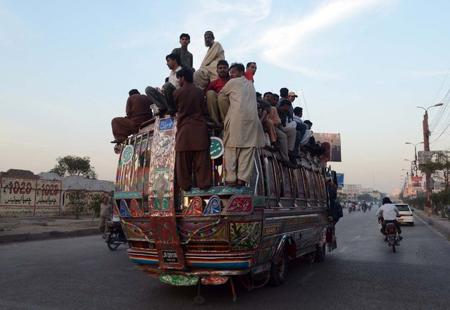 Pakistani passengers travel on a over loaded mini bus in Karachi on March 6, 2013. Karachi went on an indefinite strike , with businesses, shops, schools and transporters ordered to shutdown until police arrest those responsible for the city's worst bomb attack in years. The Muttahida Qaumi Movement (MQM), which controls most of Pakistan's largest city, ordered the strike three days after a powerful car bomb killed 50 people and wounded around 140 others in Shiite Muslim neighbourhood Abbas Town. (Photo by Asif Hassanasif Hassan/AFP Photo)