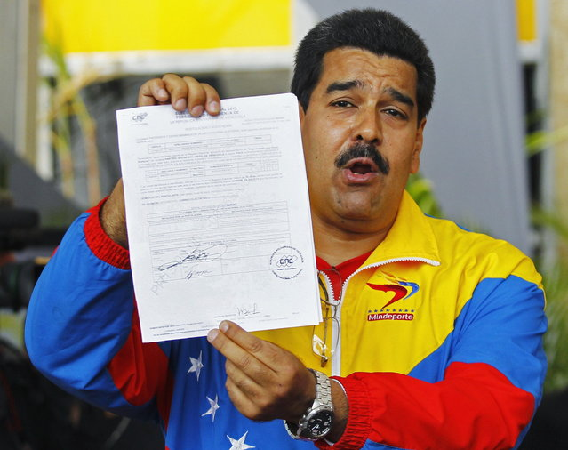 Venezuela's acting President, Nicolas Maduro, shows the document that he signed to register as candidate for president in the April 14th election at the national election board in Caracas March 11, 2013. Presidential candidates Maduro and Henrique Capriles have begun Venezuela's election race with scathing personal attacks even as mourners still file past the late Hugo Chavez's corpse. (Photo by Carlos Garcia Rawlins/Reuters)