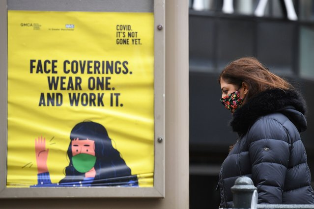 A woman wearing a facemask walks past a poster urging people to wear face coverings, in Manchester, north west England on October 13, 2020, as the number of cases of the novel coronavirus COVID-19 continue to rise. The British government faced renewed pressure on October 13, after indications it had ignored scientific advice three weeks ago for tougher restrictions to cut rising coronavirus infections. (Photo by Oli Scarff/AFP Photo)
