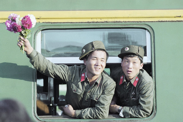 Two young North Korean soldiers, one waving flowers given to him by friends, at the window of a train before leaving Kaesong on August 22, 1990 for Pyongyang, the North Korean capital. The soldiers had ended a tour of duty at Kaesong, which is near the border dividing North and South Korea. (Photo by Vincent Yu/AP Photo)