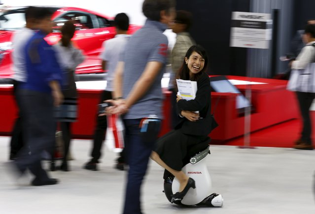A woman rides a Honda Motor UNI-CUB personal mobility device at the 44th Tokyo Motor Show in Tokyo, Japan, October 28, 2015. (Photo by Thomas Peter/Reuters)