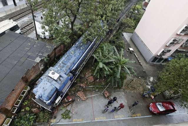 People look at a derailed train at their neighbourhood in Liuzhou, Guangxi Zhuang Autonomous Region, December 3, 2014. The train derailed and crashed into a residential complex on Wednesday morning, according to local media. The cause remains unknown and no injuries were reported. (Photo by Reuters/Stringer)