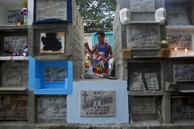 A cemetery worker repaints a grave inside a public cemetery in Makati financial district of Manila October 31, 2015. (Photo by Janis Alano/Reuters)