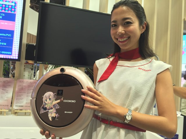 A model for Sharp Corp. shows off the electronics maker's latest vacuum cleaner featuring the Vocaloid singing voice synthesizer software at the ongoing CEATEC electronics trade show in the city of Chiba on Wednesday on October 5, 2016. The Sharp Corp. robot vacuum cleaner on display at the ongoing CEATEC trade show is no mere machine. Dubbed Cocorobo, it collaborates with a singing voice synthesizer software called Vocaloid and can hold simple conversations and even sing to people. Sharp says the idea is that a Vocaloid anime character named Cocorobo lives inside the cleaner. It listens to users and learns about them, they say, and sings songs they might like. (Photo by Kazuaki Nagata)
