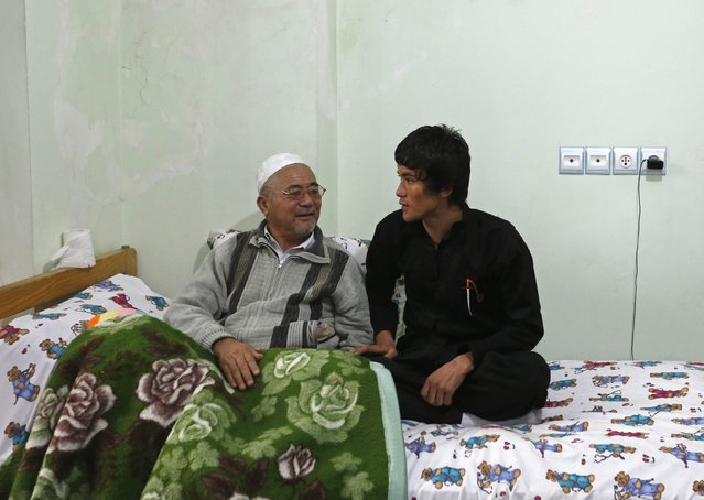 Abbas Alizada, who calls himself the Afghan Bruce Lee (R), talks to his father at their house in Kabul December 9, 2014. (Photo by Mohammad Ismail/Reuters)