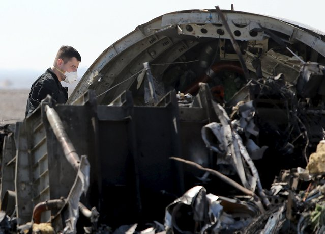 A military investigator from Russia stands near the debris of a Russian airliner at its crash site at the Hassana area in Arish city, north Egypt, November 1, 2015. (Photo by Mohamed Abd El Ghany/Reuters)