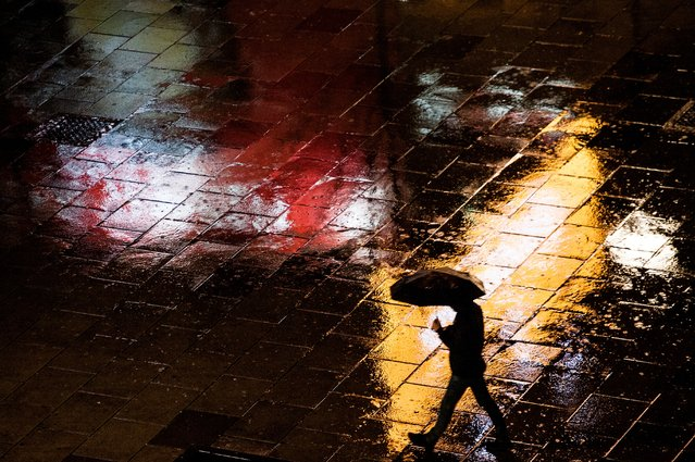 A pedestrian walks under the umbrella during a heavy rainfall on Mother Teresa square in Pristina on December 1, 2017. (Photo by Armend Nimani/AFP Photo)
