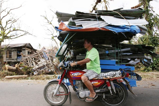 A man transports metal sheets swept by Typhoon Hagupit on the sidecar of a motorcyle in San Julian, Eastern Samar in central Philippines December 9, 2014. (Photo by Erik De Castro/Reuters)