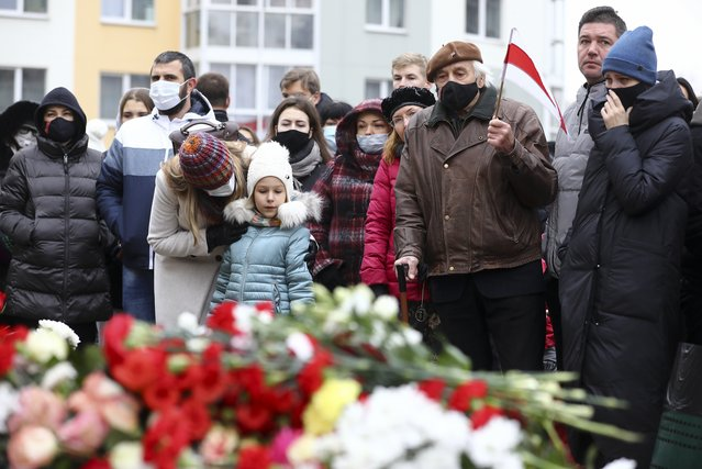 People gather to honor 31-year-old Raman Bandarenka, who died Thursday at a Minsk hospital after several hours of surgery due to serious injuries, in Minsk, Belarus, Friday, November 13, 2020. Thousands of people have rallied in Belarus on Friday following the death of a 31-year-old opposition supporter who died in a hospital after he was reportedly beaten by security forces, and the European Union condemned the continued violent crackdown that Belarusian authorities have waged on peaceful protesters. (Photo by AP Photo/Stringer)