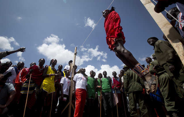 A Maasai warrior makes the high jump, in which athletes must touch a high line with the top of their heads, at the annual Maasai Olympics in the Sidai Oleng Wildlife Sanctuary near to Mt. Kilimanjaro, southern Kenya Saturday, December 13, 2014. (Photo by Ben Curtis/AP Photo)
