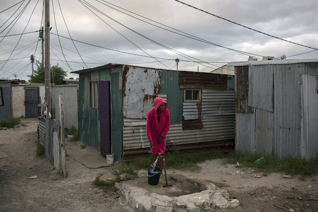 """A woman collects water in a settlement near Cape Town on Friday, February 2, 2018. South Africa's drought-hit city of Cape Town introduced new water restrictions in an attempt to avoid what it calls """"Day Zero"""", the day in mid-April when it might have to turn off most taps. (Photo by Bram Janssen/AP Photo)"""