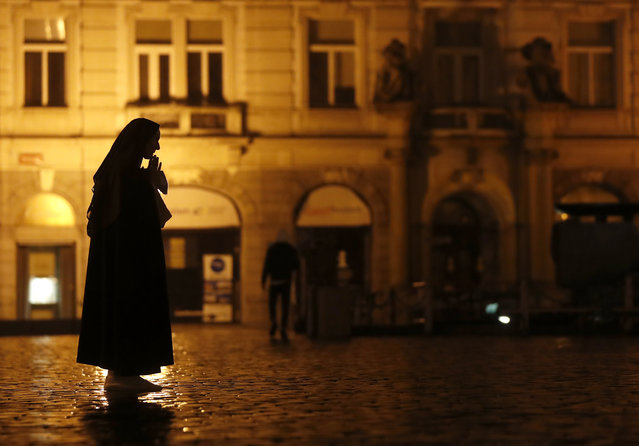 A nun prays on the near empty Old Town Square in Prague, Czech Republic, Friday, October 23, 2020. (Photo by Petr David Josek/AP Photo)