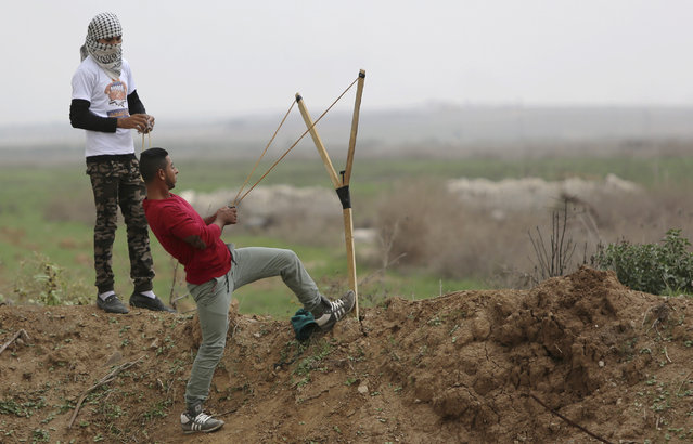 A Palestinian protester uses a sling shot to throw stones towards Israeli security forces during clashes on the Israeli border Eastern Gaza City, Friday, November 6, 2015. (Photo by Adel Hana/AP Photo)