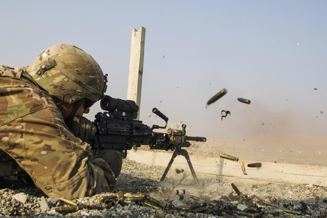 A U.S. soldier from the 3rd Cavalry Regiment is seen as he fires a squad automatic weapon during a training mission near forward operating base Gamberi, in the Laghman province of Afghanistan December 15, 2014. (Photo by Lucas Jackson/Reuters)