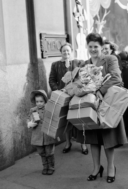 """Mrs.Frances Corless her daughter """"Chickie"""" are loaded down with bundles after doing some last minute shopping at Macy's on Christmas Eve in New York, December 24, 1946. (Photo by Carl Nesensohn/AP Photo)"""