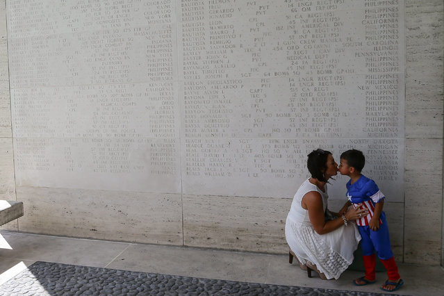 US national Mindy Warguez (L) kisses her son Tyler along a wall of names of Missing in Action soldiers during the rites for the Veterans Day ceremony at the Manila American Cemetery and Memorial in Manila, Philippines, 11 November 2015. US Ambassador to the Philippines Philip Goldberg joined the surviving war veterans in rites to honor American and Filipino troops killed in World War II at the cemetery, where more than 17,000 American military and 570 Filipino counterparts are buried. (Photo by Mark R. Cristino/EPA)