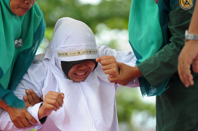 A Muslim girl gets taken to be caned 23 strokes after being caught in close proximity with her boyfriend in Banda Aceh on October 17, 2016. Out of seven couples caught spending time together outside marriage, 13 were caned while one girl was spared after it was discovered that she was pregnant. Indonesia's Aceh province has gained international infamy for its strict Islamic laws. (Photo by Chaideer Mahyuddin/AFP Photo)