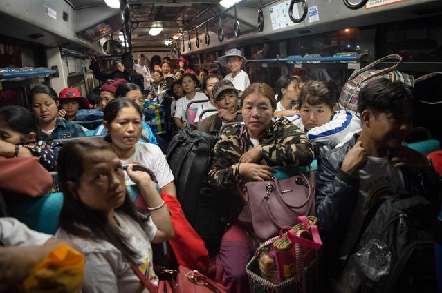 Ethnic Kachin Catholic faithful take buses to a Catholic church after arriving at the railway station in Yangon on November 25, 2017 ahead of the arrival of Pope Francis. Pope Francis arrives in Myanmar on November 27, locked in the headwinds of global outcry over the country's treatment of its minority Muslim Rohingya, some 620,000 of whom have been driven out of Rakhine state since August. (Photo by Ye Aung Thu/AFP Photo)